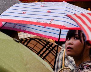 woman holding umbrella looking upwards